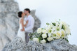 Bouquet and wedding couple kissing behind