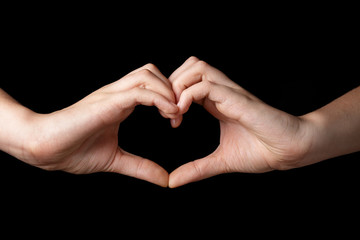 female teen hands showing heart symbol