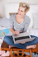 blonde frau bucht urlaub am computer
