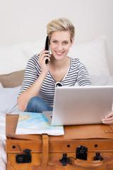 frau bucht reise mit computer und telefon