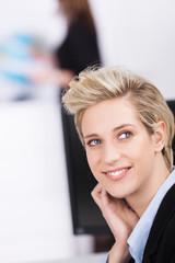 blonde frau im büro schaut zurück