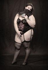 Retro style picture of an overweight woman dressed in corset.