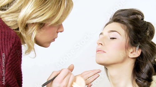 Makeup artist retouching lip of model