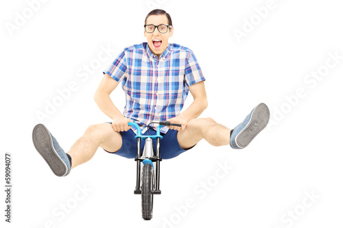 Crazy young man posing on a small bicycle