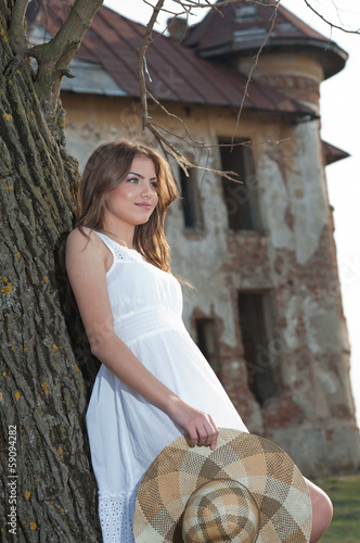 Pretty young woman posing in front of the farm. Very attractive