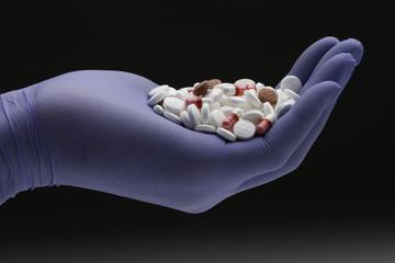 Hand in blue glove holding prescription pills, horizontal