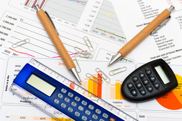 Calculator and pencil on the paper with financial graph's
