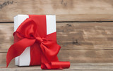 paper gift box wrapped with red ribbon on wood background