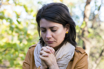 Portrait of young woman praying in nature