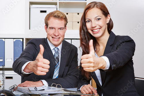 Two business people holding thumbs up