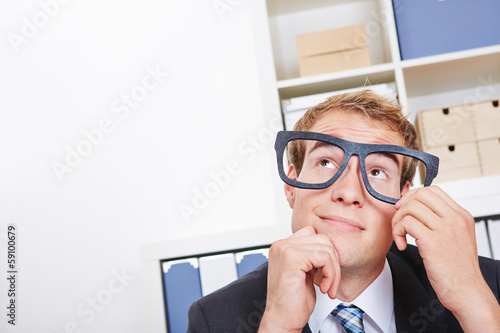 Pensive business man in office with nerd glasses