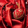 Red christmas velvet ball with gold pattern on folds of red clot