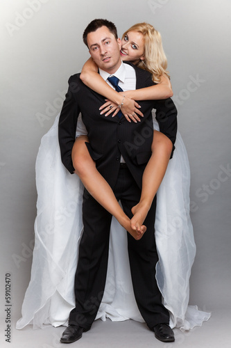 Cheerful wedding couple having fun bride groom embracing