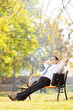 Young businessman seated on a bench relaxing in a park