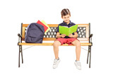 Schoolboy seated on a wooden bench reading a book