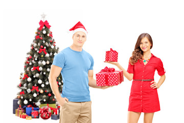 Smiling couple holding gifts in front of a christmas tree