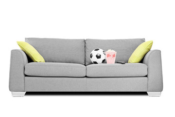 Studio shot of a modern couch with soccer ball and popcorn box