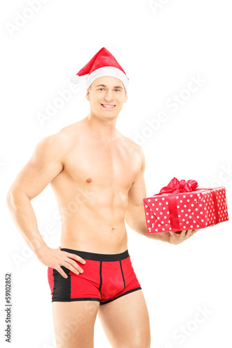 Handsome guy wearing red underpants and christmas hat and a gift
