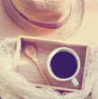 Straw hat with black coffee and spoon on wooden tray, retro filt