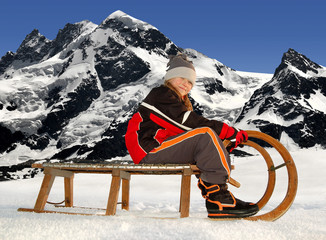 Girl on a sleigh,in the Swiss Alps