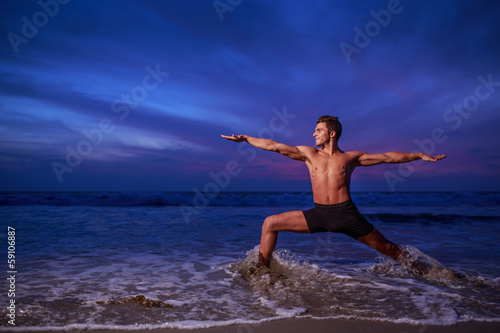 Man in yoga warrior pose standing in ocean water