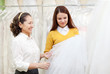 Two women chooses bridal veil