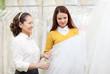 Two women chooses bridal veil