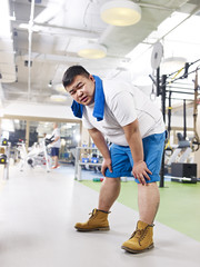 exhausted overweight man in gym