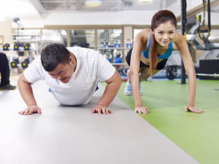 overweight man and fit young lady doing pushups