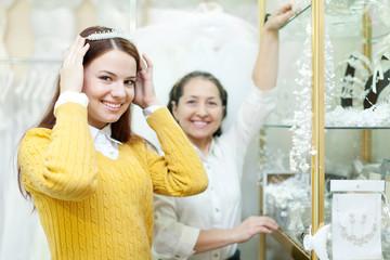 woman helps the bride in choosing bridal diadem