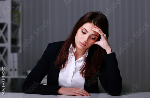 Young sad businesswoman sitting at the table