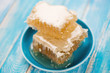 Honeycomb pieces in a saucer, horizontal shot