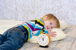 Tired toddler lying down with alarm clock in front