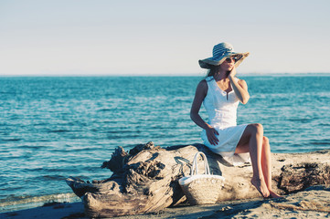 Young woman wearing white dress relaxing at the beach.