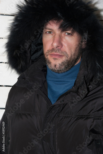 Portrait of confident man wearing fur hooded parka coat at the w