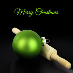 Christmas ball with rolling pin on black background