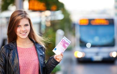 Mädchen an einer Bushaltestelle hält 10 Euro