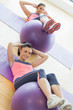 Two young women exercising with fitness balls at gym