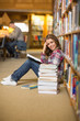 Pretty happy student reading book on library floor