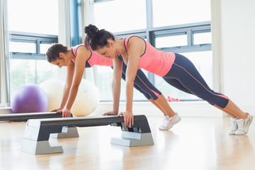 Two fit women performing step aerobics exercise in gym