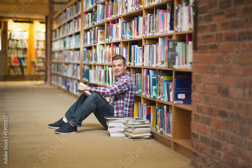 Smiling student sitting on library floor reading