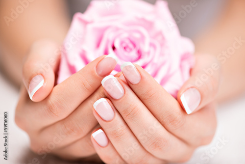 Leinwandbild Motiv Beautiful woman's nails with french manicure  and rose