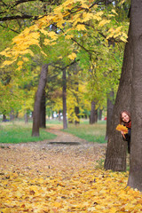 Smiling woman in the park with autumn leaves