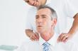 Chiropractor massaging patients neck