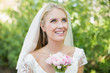 Pretty smiling bride holding her bouquet wearing a veil looking