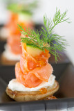 Blini with smoked salmon and sour cream, garnished with dill