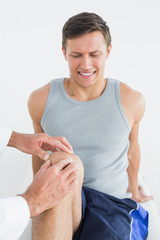 Displeased young man getting his knee examined