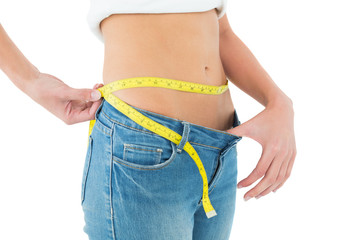 Mid section of woman measuring waist in a big sized jeans
