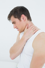 Side view of a young man suffering from neck pain