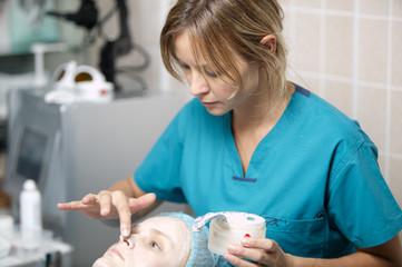 Nurse in a skin clinic applying protective cream